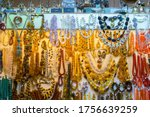 Many types of jewelry: amber, coral and precious stones beads, many other jewelry and metal souvenir figures. Showcase of souvenir store, Cloth Hall (Sukiennice) Krakow, Poland.