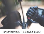Small photo of Close up car thief hand holding screwdriver tamper yank and glove black stealing automobile trying into glass door window edge to see if vehicle is unlocked trying to break inside.