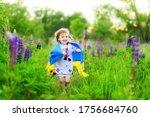 Child carries fluttering flag of Ukraine in field. Ukraine