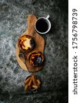 Small photo of Pastel de Nata. Traditional Portuguese dessert, egg tart on the board with cup of coffee and cinnamon sticks in the strainer over metal rustic background. Top view