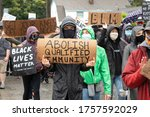 """Small photo of Seattle, Washington / USA - June 12 2020: Protester with """"Abolish Qualified Immunity"""" sign at the March of Silence in support of Black Lives Matter"""