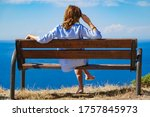 Woman Sitting On A Cliff Bench...