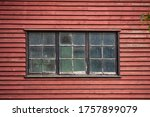 Old weathered rustic and dirty windows in in an old red painted wooden building. Close-up image from the outside.