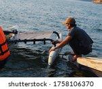 Kanchanaburi, Thailand, 22 February 2020; Man preparing kayak with float wings at the pier - stock photo