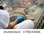 Woman Restoring An Ancient...
