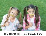 Small photo of Ready for party. Little children hold mustache props green grass. Small girls with photobooth props on sticks. Party props and accessories. Perfect props for celebration. Summer holidays.