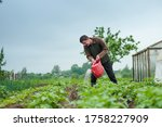 Portrait of Young Gardener water the flowers from his plastic watering can. Man farmer working in his own garden. Summertime in a country village. Close up. Unity with nature, relax and meditation. - stock photo
