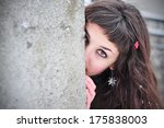 Stock photo shy woman hiding behind wall face laughing timid 175838003