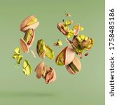 Small photo of Flying in air fresh raw whole and cracked pistachios isolated on green background. Concept of Pistachios is torn to pieces close-up. High resolution image