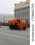 """Small photo of MOSCOW/RUSSIA-05.09.2019.After the Parade, orange KAMAZ trucks in soccer balls clean the street. The inscription on the Board is """"the Art of well-maintained roads"""".The ninth of may."""