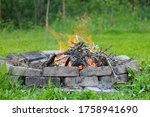 Small photo of Refractory brick campfire in focus and blurred bonfire green grass in the background