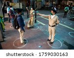 Small photo of MUMBAI/INDIA -JUNE 17, 2020: Police wearing mask monitor body temperature of people at Chhatrapati Shivaji Maharaj terminus India has begun gradually lifting its restrictions imposed by the government