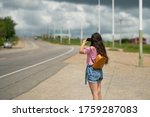 Small photo of tourists with backpacks hitchhiking on road. Hitchhiking tourism concept. Travel hitchhiker girl walking on road. girl photographs on camera phone