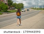 Small photo of Girl tourists with backpacks hitchhiking on road. Hitchhiking tourism concept. Travel hitchhiker girl walking on road. Girl in the pink t-shirt and denim shorts walking near the road.
