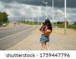 Small photo of Girl in the pink t-shirt walking near the road. Tourists with backpacks hitchhiking on road. Hitchhiking tourism concept. Travel hitchhiker girl walking on road. girl photographs on camera phone.