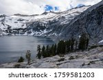 Snowmelt has filled a high mountain lake in the Sierra Nevada mountains in California. These scenic mountains, that rise between 5,000 and 9,000 feet, provide amazing wilderness areas for hikers. - stock photo