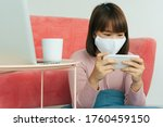 Beautiful young asian thai black short hair woman wearing white surgical doctor mask and playing game on smartphone at home. - stock photo