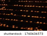 Many Lit Candles Stand In Rows...