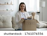 Small photo of Close up woman sit on sofa near big cardboard box full of new clothes, old stuff used apparels is prepared for donation. Help for poor needy people, humanitarian aid, charity and benevolence concept