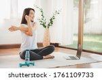 Smiling Asian Woman Doing Yoga...