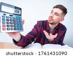 Small photo of Miscalculation. Error in calculations. Unexpected result. A man in a checked shirt gestures and shows a number on a calculator. A wide-eyed man with a calculator in his hands.
