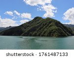 Beautiful green pine trees on rocky mountains with green water front during summer with nice blue sky and clouds background  in dam of Ridracoli, Province of Forli-Cesena, Italy