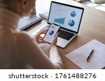 Small photo of Woman hold smartphone use pc at workplace. Project stats financial data sales charts on laptop and cellphone screen, close up view over shoulder. Report preparation, synchronization for safety concept