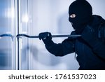 Intrusion Concept. Side view portrait of disguised prowler breaking house or office door with crowbar - stock photo