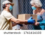Small photo of Young male volunteer in mask gives an elderly woman boxes with food near her house. Son helps a single elderly mother. Family support, caring. Quarantined, isolated. Coronavirus covid-19. Donation