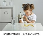 Small photo of A glass of water and fish oil pills. A child plays doctor in the children's room, a scattering of yellow capsules on the table, a bear cub takes omega 3 pills. a Child with a stethoscope in his ears.