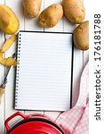 recipe book with potatoes on kitchen table - stock photo