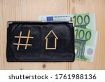 A straw hashtag sign, as a symbol of social networks, and a straw house, as a symbol of a mortgage, lie on a black wallet with evo banknotes. Discussion of mortgages on social networks