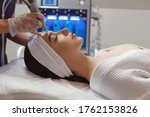 Small photo of Side view of woman receiving microdermabrasion therapy on forehead at beauty spa