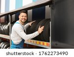 Mechanic near rack with car tires at service station - stock photo