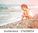 Girl With Pebbles On The Beach
