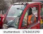 A Worker In An Orange Vest Sits ...