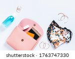 Small photo of Woman purse with fashionable face masks, hand sanitizer, smartphone and cosmetics on white table top, new normal concept. Stylish protective masks and fashion accessories, copy space
