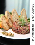 Small photo of Raw tartar meat with spices, croutons and herbs. Beef tartar with capers. Beef tartar with slices of bread. Raw meat tartare for gourmet meat.