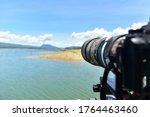 Camera telescope, telephoto lens finding bird in wildlife lake and blue sky.