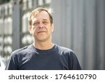 Small photo of Street portrait of a man 40-50 years old in a black t-shirt on a neutral blurred background. Perhaps he is just a buyer, an actor or a truck driver, a loader or a military pensioner
