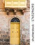Small photo of A traditional Maltese wooden door, painted yellow, and stone facade of a traditional old Maltese house.