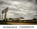 A rusty metal motel sign with wooden old motels under the cloudy and rainy  sky