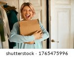 Small photo of Indoor image of happy cheerful young woman holding cardboard box delivered to her apartment, expressing excitement, going to unpack parcel, having impatient overjoyed look. Food delivery and shopping
