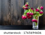Small photo of Beautiful listless roses with leaves in a glass on a dark wood background. Great wood background with dry roses and copy space.