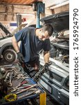 Car master mechanic working in auto vulcanizing and vehicle service workshop - stock photo