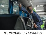 Public Coach Bus Driver With Protective Face Mask On Checking Air Fan Above Passenger Seats.  - stock photo