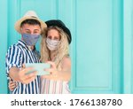 Small photo of Young couple wearing face mask taking selfie with mobile smartphone on vacation - People having fun traveling again during corona virus outbreak - Love relationship and technology concept