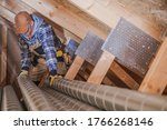 Small photo of Male Ventilation Technician Installing New Air Vent System In Attic Of Residential Building.