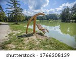 Small photo of A wooden swing over Lake Bloke in Nova Vas, Slovenia on a sunny day