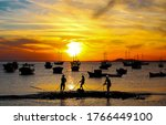 Sunset fishing at sea shore. Fishermen silhouettes at sunset. Sunset fisherman silhouette